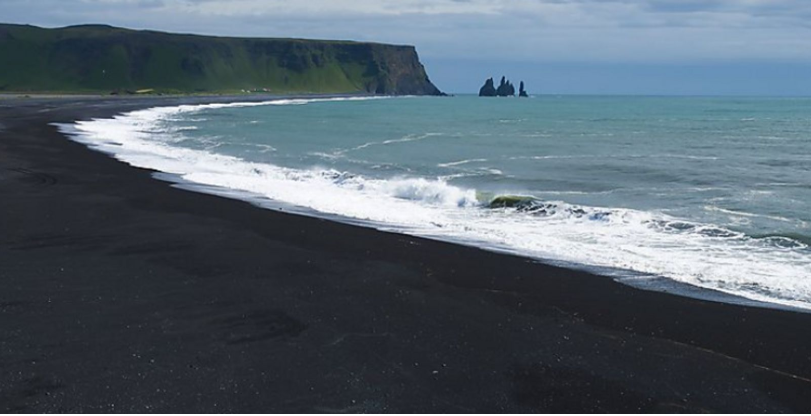 black sand beach with sea stacks in the distance in Iceland