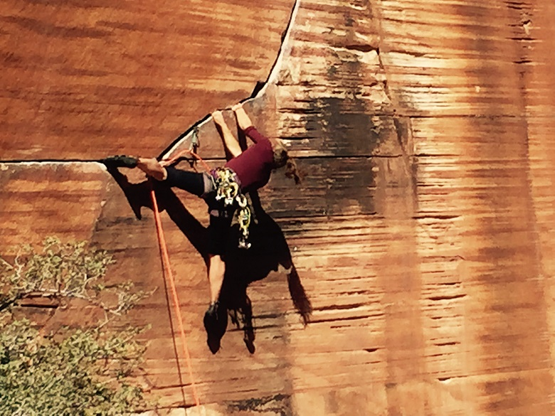 woman climbing crack in red sandstone