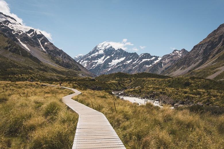 boardwalk through meadow valley toward snowy mountain peaks