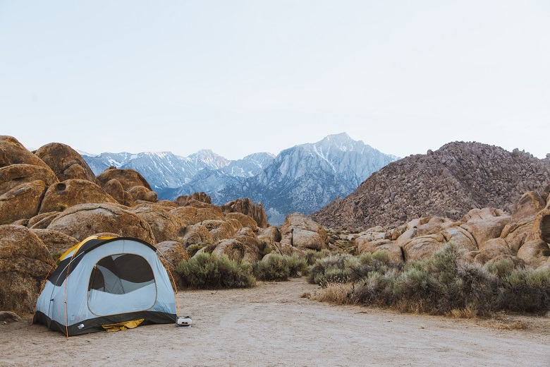 Tent on flat dirt area among boulders with snow mountain peaks in the background