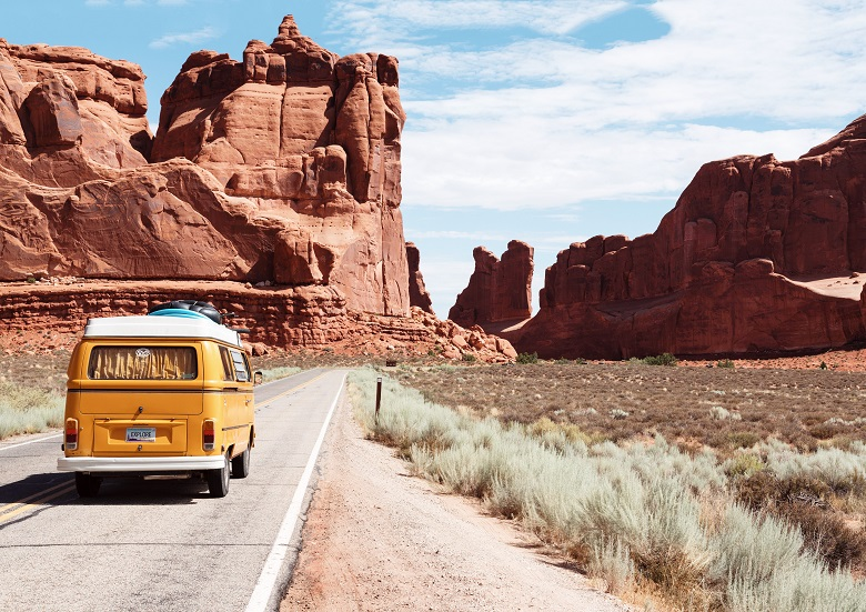 yellow campervan on desert road surrounded by red sandstone cliffs