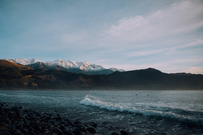 sea waves with snowy mountains in the background