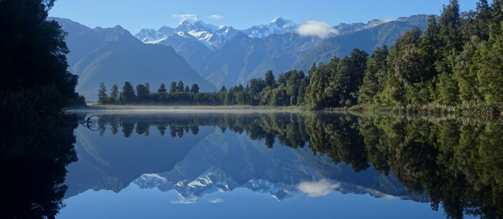 snowy mountain range reflected in lake