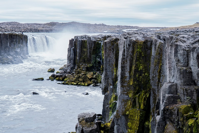 waterfall in middle of river with sheer grey cliffs