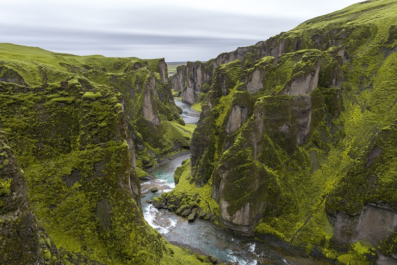 river winding through narrow canyon with green vegetation on its steep cliffs