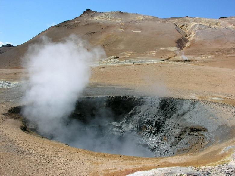 crater with steam in front of brown hill