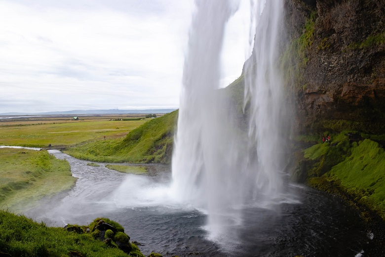 People wearing red raincoats standing behind a powerful waterfall