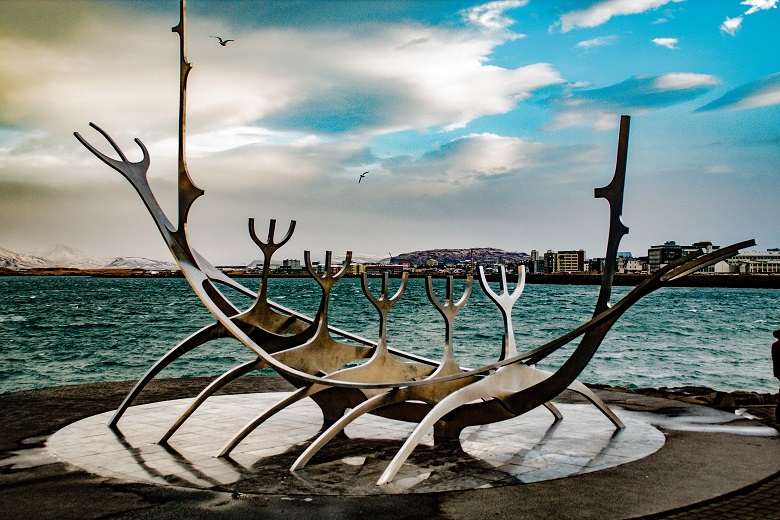 sculpture of boat skeleton in front of body of water and city