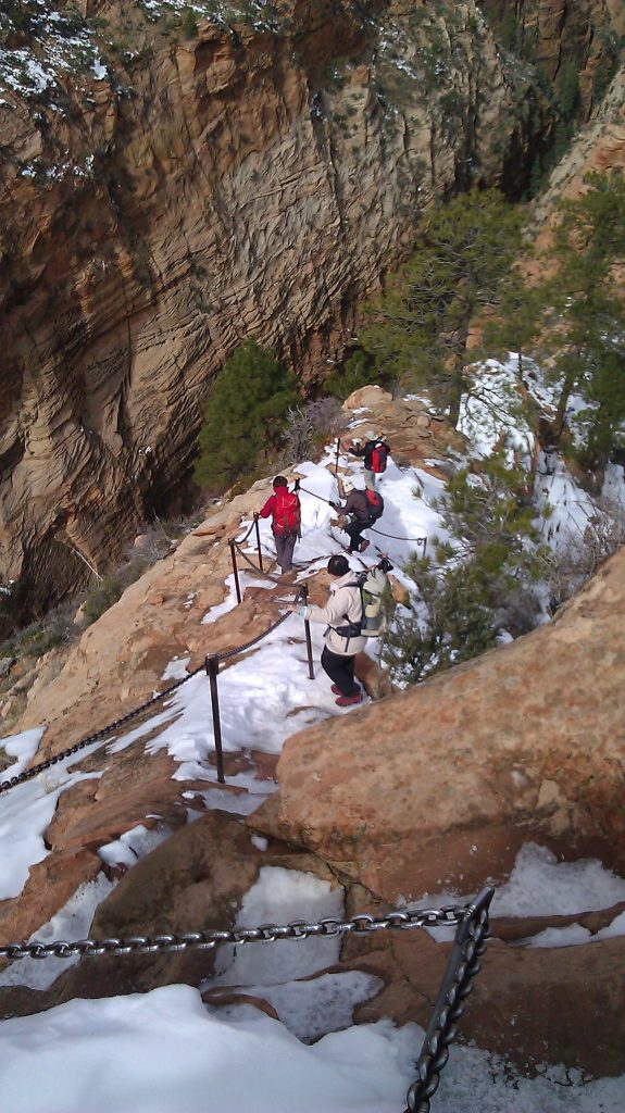 people hiking down steep snowy path marked by chains